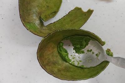 アボカドの緑の実の部分をこそげる