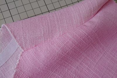 縫製中のコチニール染めの麻生地